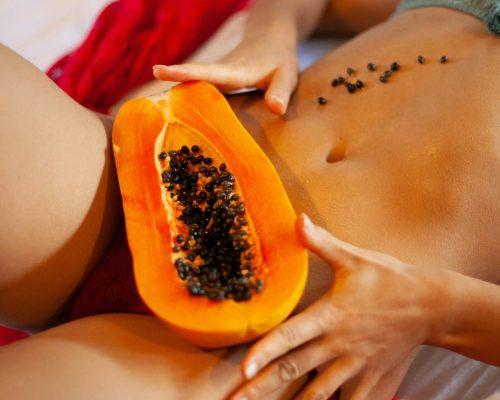 Frau mit Papaya als Andeutung für die Vulva