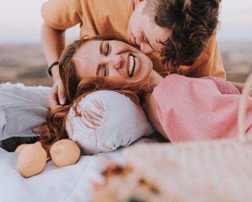 Mann küsst Frau auf die Wange, Frau entspannt und lacht